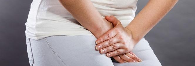 Frau hält sich den Unterleib wegen einer Blasenentzündung