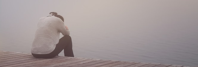 Frau, die am Wassersitz und sich ausgebrannt fühlt