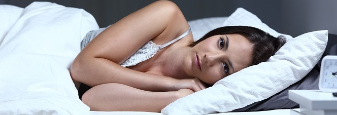 Frau, die schlaflos im Bett liegt